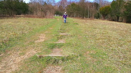 Woman on a country walk walking down some steps on a hill