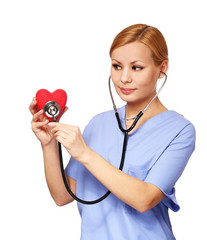 Nurse with stethoscope examining red heart, isolated on white
