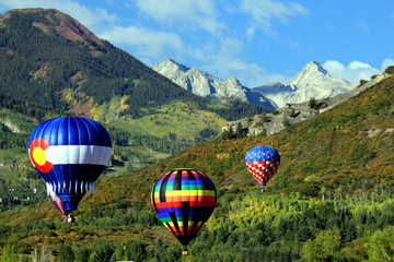 Hot air balloons floating through the Rocky Mountains