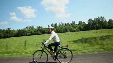 Slow motion - Woman cycling on road in countryside