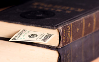 Large vintage book with dollar cash note used as tab
