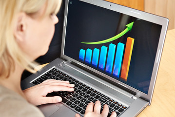 Business woman looking at graph of growth indicators on laptop