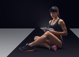 Fitness sporty woman using a digital tablet