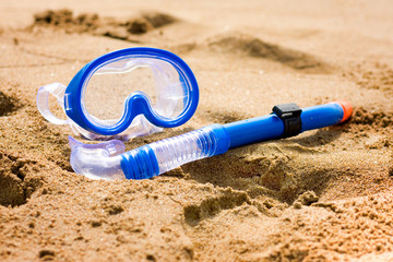 Blue snorkel and diving mask on beach