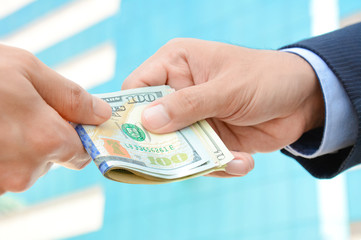 Hand receiving money, US dollars, from businessman