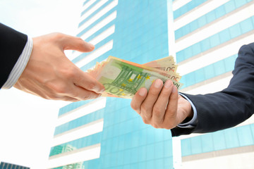 Businessman hands giving & receiving money - Euro currency (EUR)