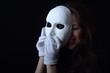 brunette girl holding a white theatrical mask - 81277256