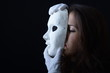 brunette girl holding a white theatrical mask - 81277261