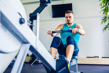 Crossfit instructor at the gym doing Rowing Exercise