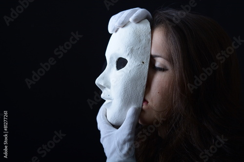 Leinwanddruck Bild brunette girl holding a white theatrical mask