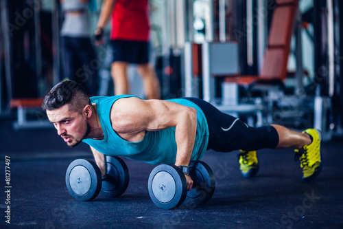 Poster Fitness Crossfit instructor at the gym doing pushups