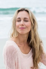 Smiling pretty blonde relaxing on the sand