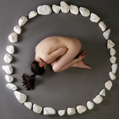 Nude woman lying in circle made of stones