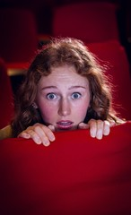 Young woman watching a scary film