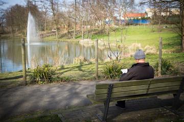 älterer mann auf einer parkbank