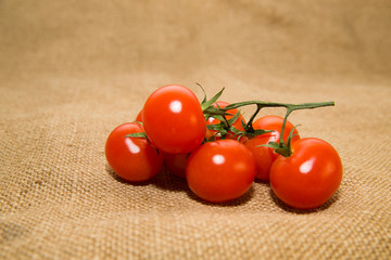 Bunch of red cherry tomatoes on old cloth