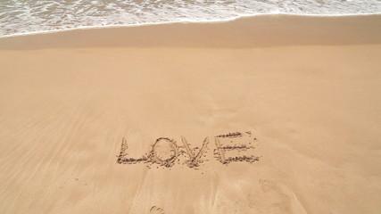 Ocean wave approaching word love written in sand