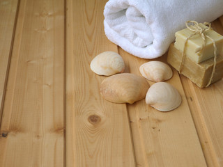 Towel,soap,and shells on the wooden background