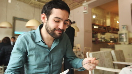 Handsome young man eating in a restaurant