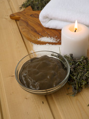 Mud,candle and towel on the wooden background