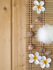 Shells and tiare flowers on the wooden background