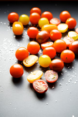 Multicolored cherry tomatoes on a black background