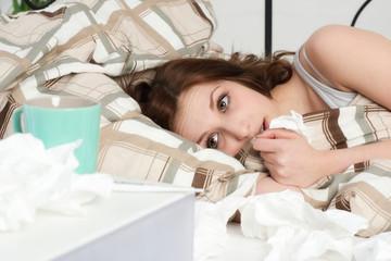 Junge Frau liegt erkältet im Bett