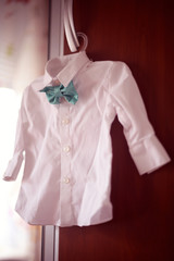 Cute smal shirt with green bowtie hanging
