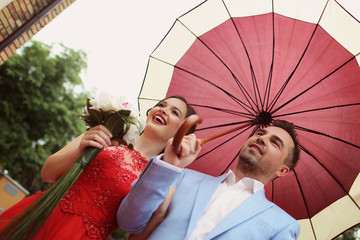 Beautiful couple with red umbrella on a rainy day