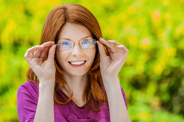 Beautiful red-haired smiling young woman with glasses.