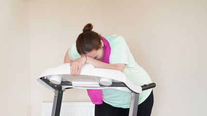 Corpulent woman running with perseverance on a treadmill
