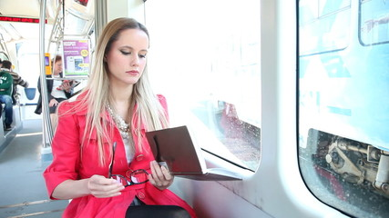 Beautiful woman sitting in tram put her glasses on and starting to read