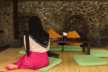Mujer musulmana sentada en el suelo.