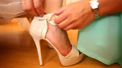Woman helping bride to put beautiful wedding shoes on