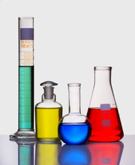 Volumetric laboratory glassware containing colored liquids isola