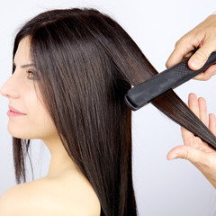 Beautiful woman getting long silky hair straightened
