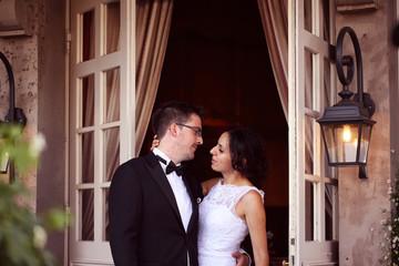 Bride and groom near door with windows