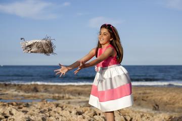 Niña con vestido de fiesta cogiendo bolso en el aire