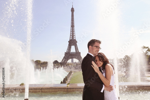 Bride and groom hugging at fountain in Paris Poster