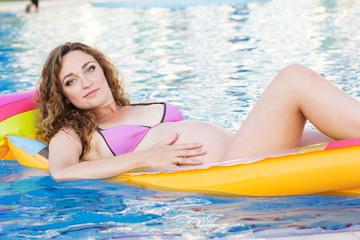 Pregnant girl on mattress in swimmimg pool