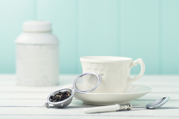 Tea time: a cup and a tea infuser on a white table. Vintage