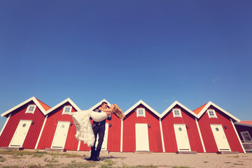 Bride and groom near red houses on their wedding day