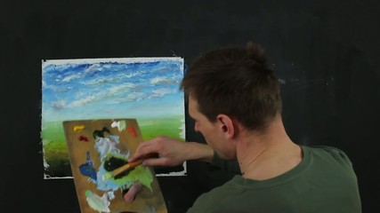 Artist working on painting. Process of creating art on canvas.