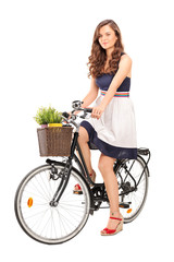 Young woman posing seated on a black bicycle