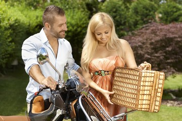 Happy casual couple with scooter and picnic basket