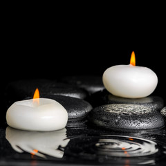 beautiful spa concept of white candles and black zen stones on r