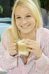 Frau im Schlafanzug trinkt Milchkaffee