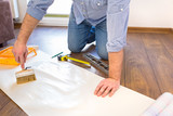 Handyman applying blue for a wallpaper - 81291042