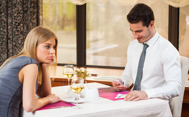 Woman is bored at restaurant, her boyfriend is typing sms