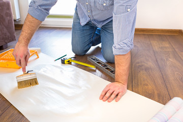 Handyman applying blue for a wallpaper